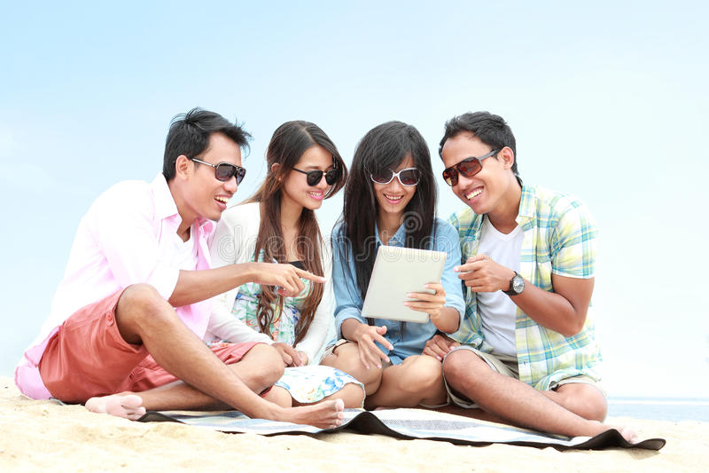 Groupez les amis appréciant des vacances de plage ainsi que le PC de comprimé photos libres de droits