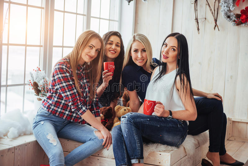 Groupez les beaux jeunes appréciant en conversation et café potable, filles de meilleurs amis ayant ensemble l'amusement photos stock