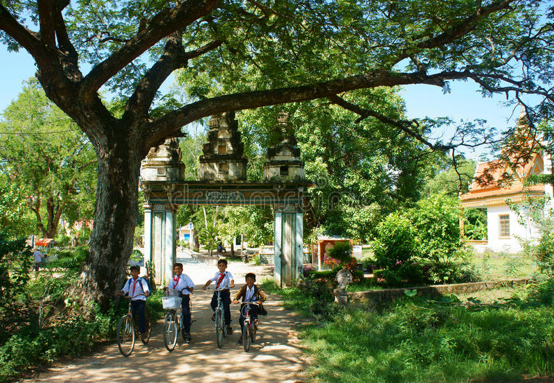 Groupez les enfants asiatiques, vélo de monte, porte de village de Khmer photographie stock libre de droits