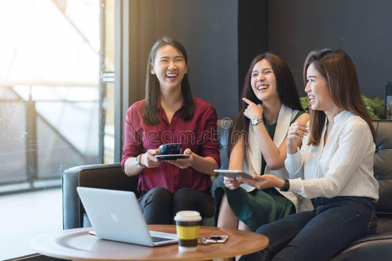 Groupez trois femmes se réunissant dans un café causant à chaque othe photo stock
