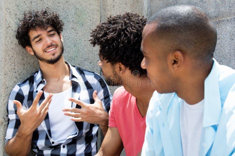 Groupon afrikansk amerikan en caucasian hipsterman i diskussion royaltyfria bilder