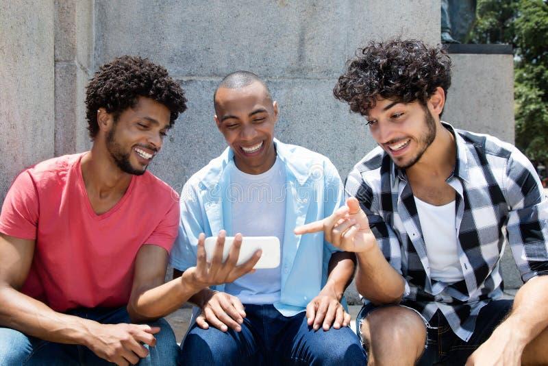 Groupon afrikansk amerikan en hållande ögonen på sport för caucasian hipsterman royaltyfria foton