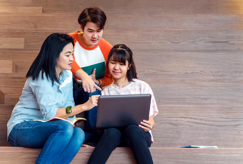 Groups of asian teenage students using laptop computer studying stock image