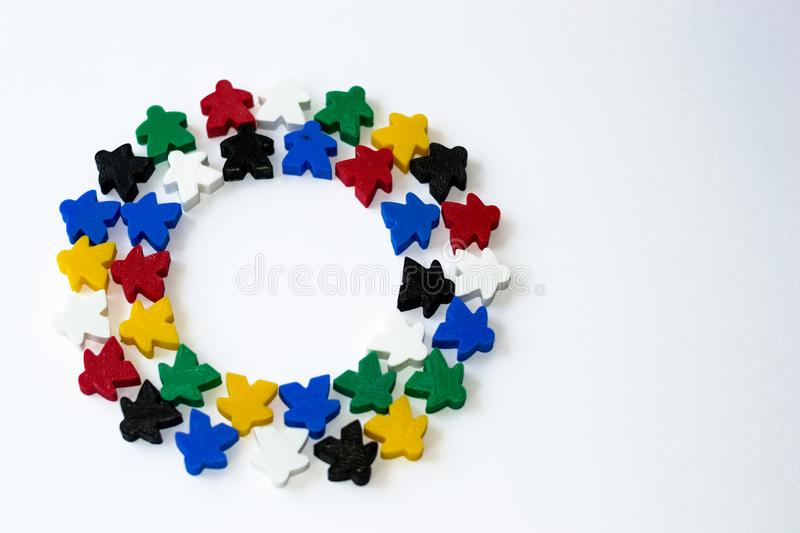 Groups of colorful meeples in circle isolated on gray background. Colorful round frame of game components. Small figures of man. stock images
