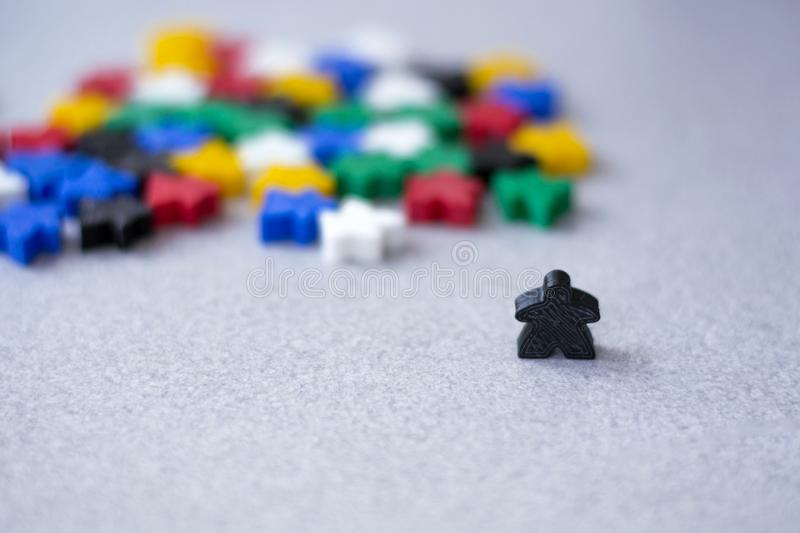 Groups of colorful meeples isolated on gray background. Small figures of man. Board games concept. Leader of people nation. royalty free stock photography
