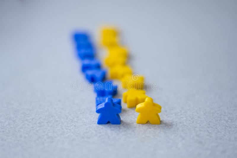 Groups of colorful meeples of two teams. Colors of ukrainian flag - blue and yellow. Small figures of man stock photo