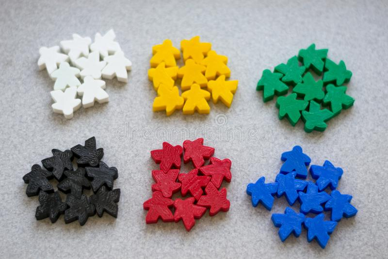 Groups of colorful meeples of two teams. Colors of ukrainian flag - blue and yellow. Small figures of man royalty free stock image