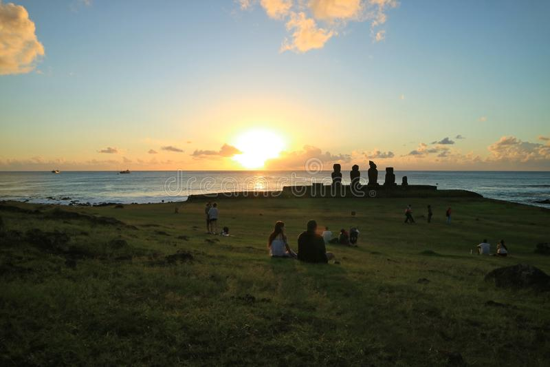 Groups of people watching sunset at Ahu Tahai on the Pacific ocean coast, Archaeological site on Easter Island, Chile stock image