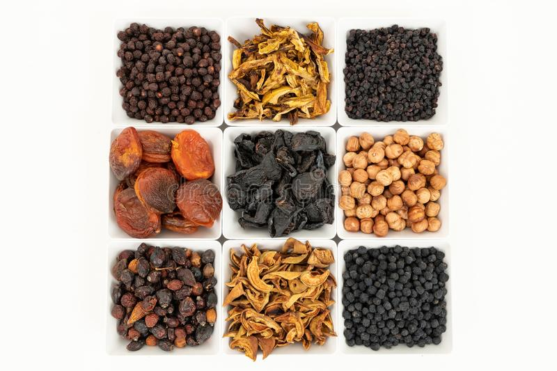 Groups of various kinds of dried fruits in square white bowls on white background stock photos