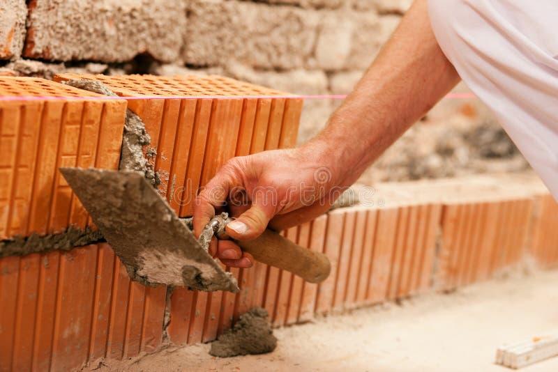 grout bricklayer кирпича делая стену стоковые фото