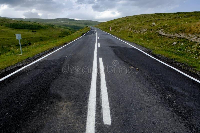 Grov asfaltbeläggningväg till ingenstans mellan dalar royaltyfri fotografi