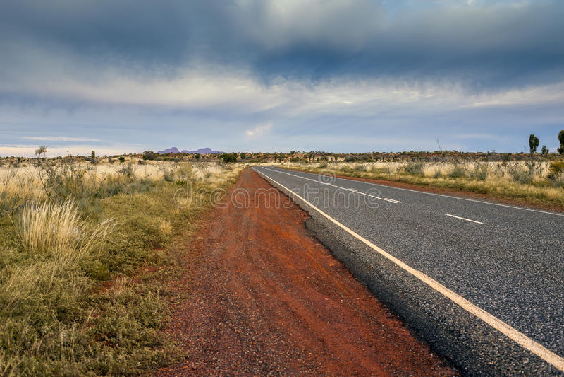 Grov asfaltbeläggningvägen leder till ingenstans i australisk öken i stormigt moln royaltyfri fotografi