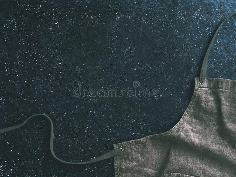 Grov bomullstvillbomullsförkläde på mörk bakgrund, kopieringsutrymme arkivfoton
