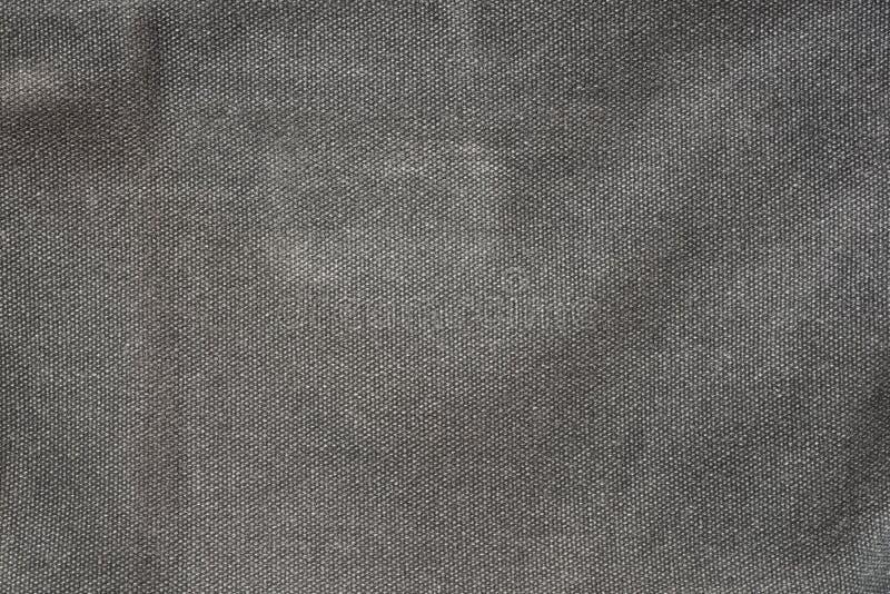 Grov mörk grå bakgrund för tygtextiltextur royaltyfria foton