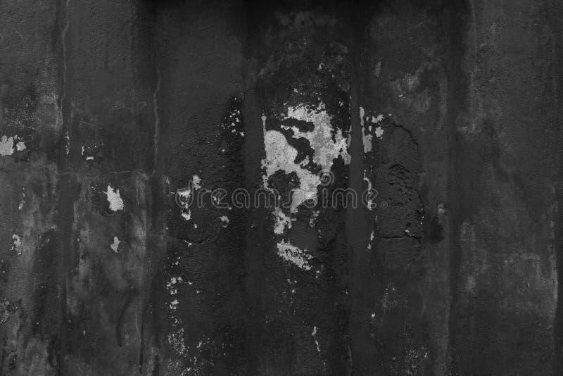 Grov svart målad betongvägg med sprickor och chiper i murbruk royaltyfri foto