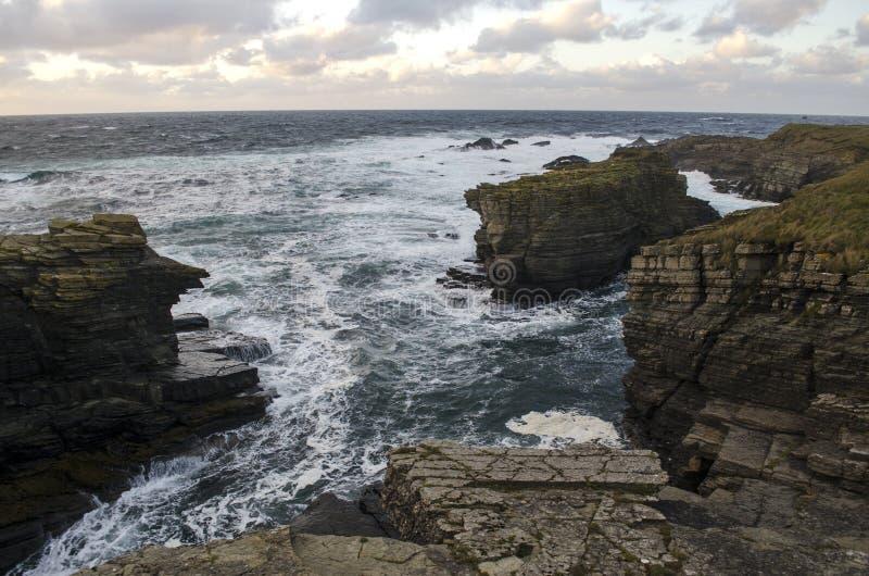 Grova vågor förbi kust- klippor arkivbilder