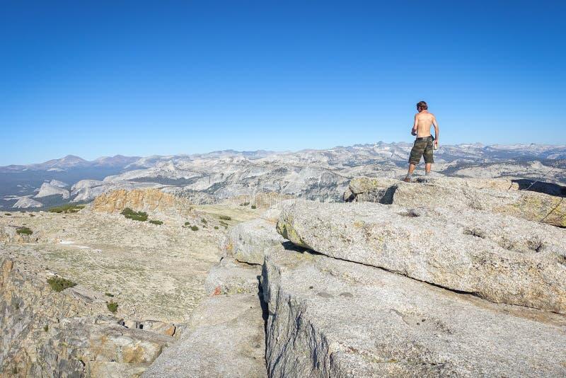 Groveland,加利福尼亚-美国- 2014年7月24日:检查他的电话的一个赤裸上身的远足者在Mt顶部 霍夫曼,在nat的优胜美地 免版税图库摄影