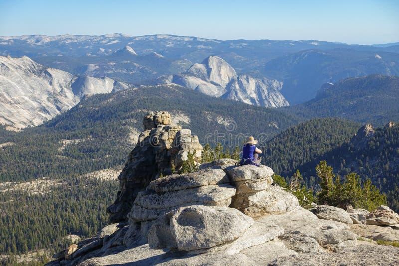 Groveland, Калифорния - Соединенные Штаты - 24-ое июля 2014: Женщина отдыхает gazing вне над половинными куполом и долиной Yosemi стоковые изображения rf