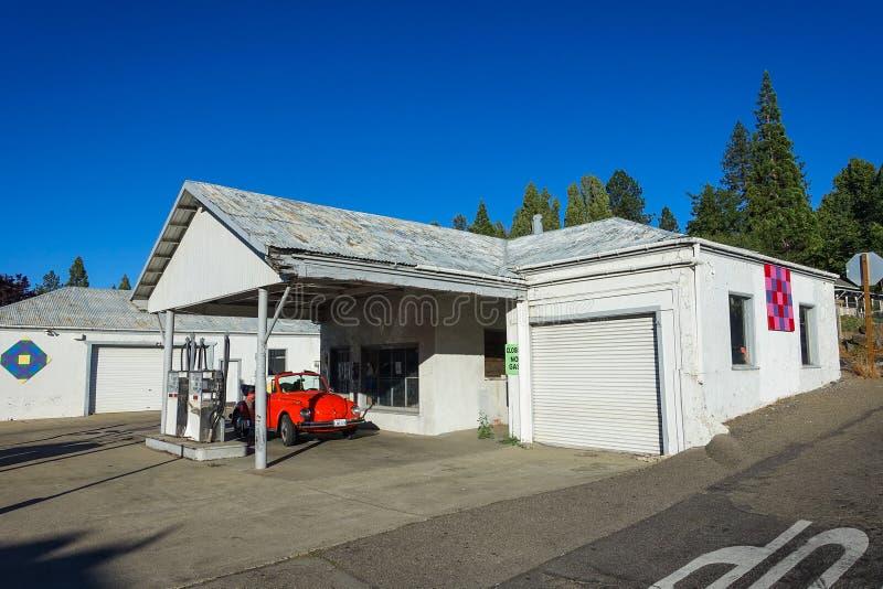 Groveland, Californië - Verenigde Staten - Juli 22, 2014: Klassiek rood Volkswagen Beetle zit geparkeerd bij een verlaten benzine stock foto