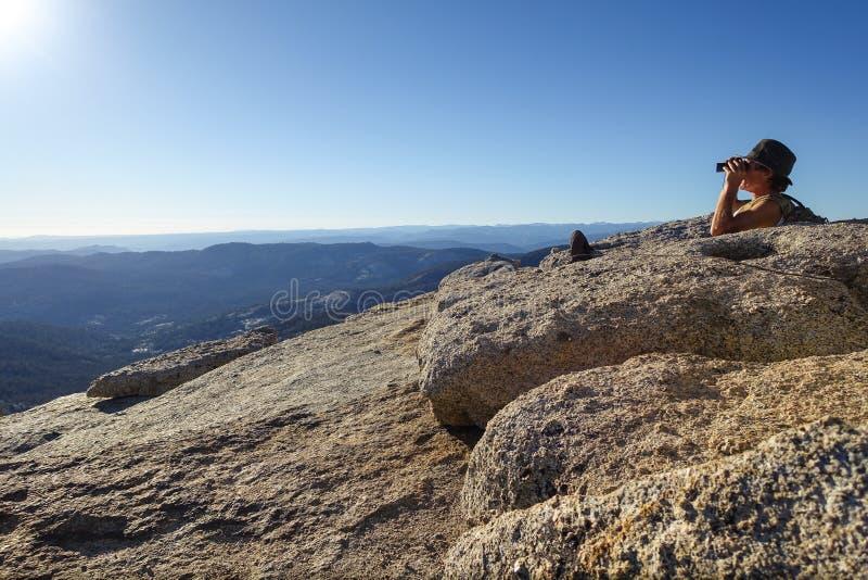 Groveland, California - Estados Unidos - 24 de julio de 2014: El hombre busca con los prismáticos después de caminar al top de Mt foto de archivo