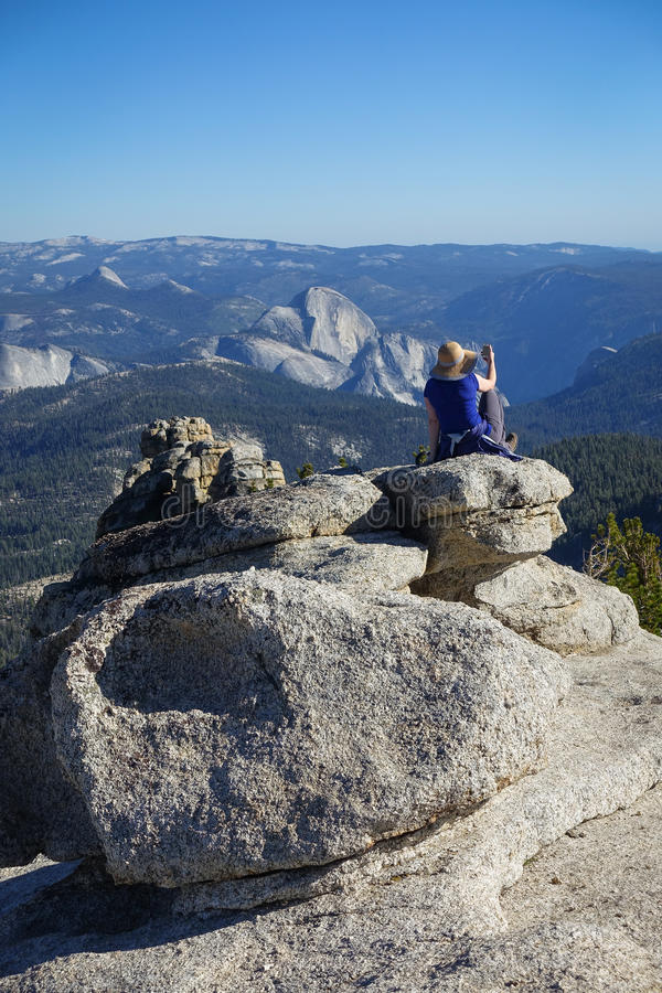 Groveland, California - United States - July 24, 2014: A woman takes a photo of Half Dome in Yosemite National Park. This peak can be reached via a 1.5 hour stock photos