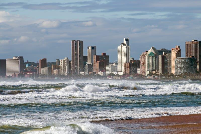 Grovt hav mot blå molnig stadshorisont i Durban royaltyfria foton