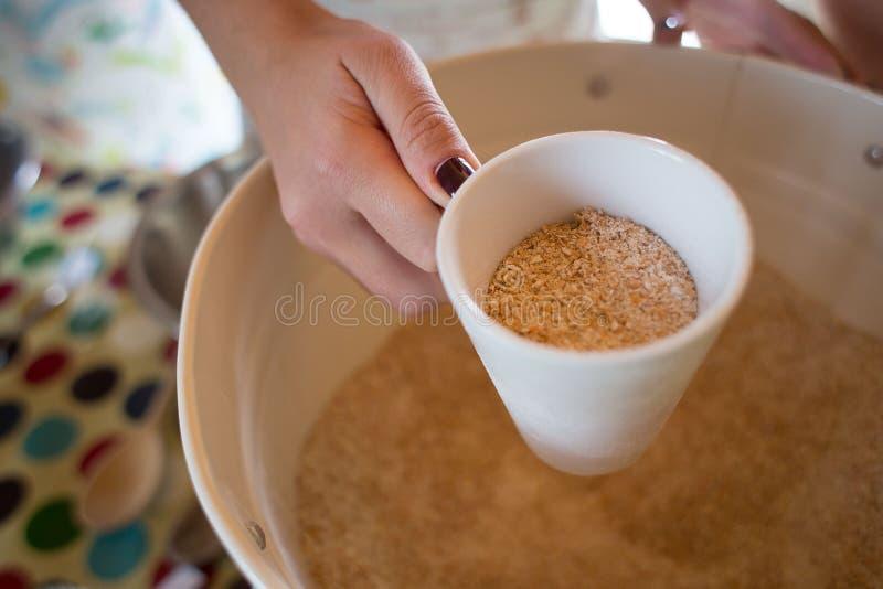 Grovt mjöl i en hink, mjöl i en vit kopp arkivbild