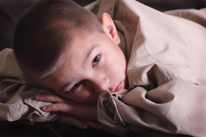 Grow into Daddy's Big Shirt. A cute solemn young boy with dark eyes wearing and wondering if he will ever grow into Daddy's big shirt royalty free stock photography