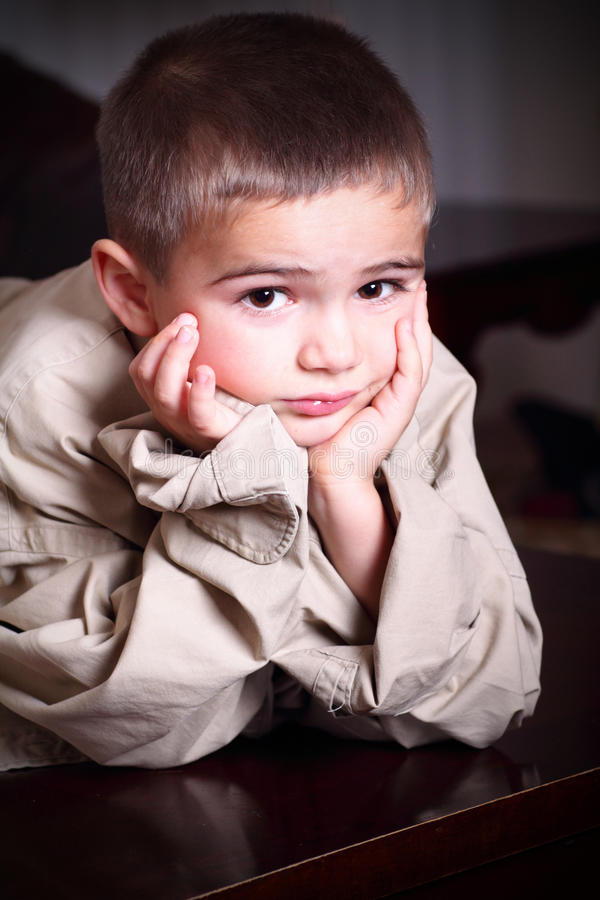 Grow into Daddys Shirt. A cute little boy with dark eyes wearing and wondering if he will ever grow into Daddys big shirt royalty free stock image