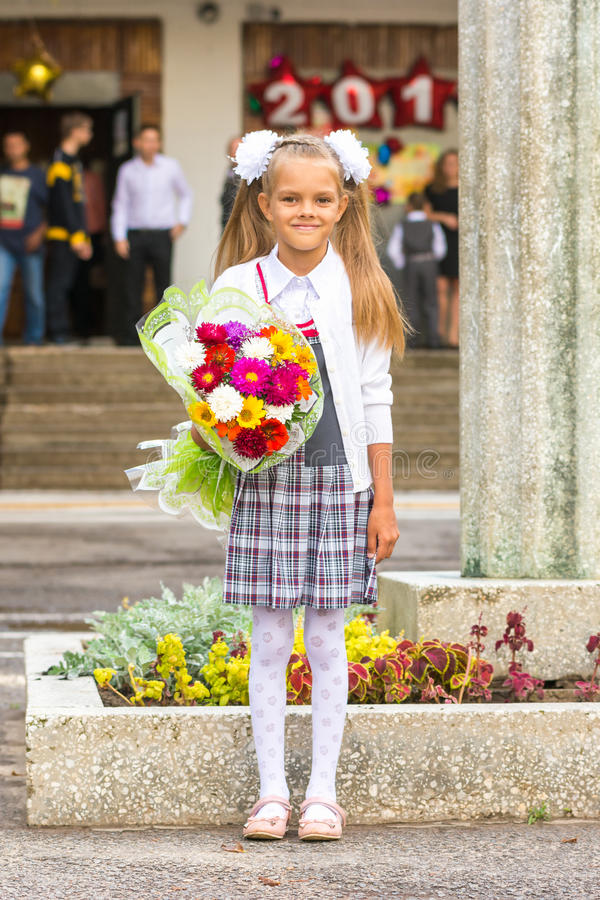 Grower Baby girl first-grader with bouquet of flowers at the school royalty free stock image