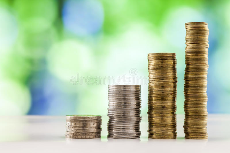 Growing coins stacks with green and blue sparkling bokeh background. Financial growth, saving money, business finance wealth and stock photos