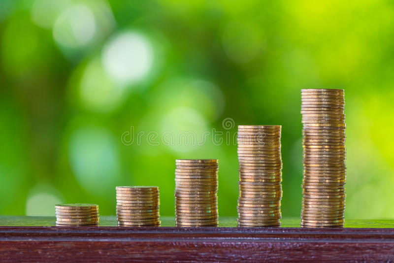 Growing coins stacks with green bokeh background. Financial grow royalty free stock images
