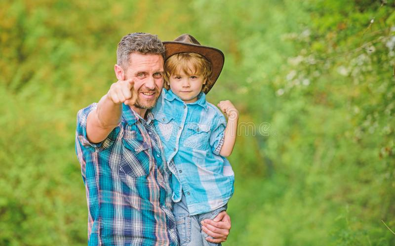 Growing cute cowboy. Small helper in garden. Little boy and father in nature background. Spirit of adventures. Strong royalty free stock images
