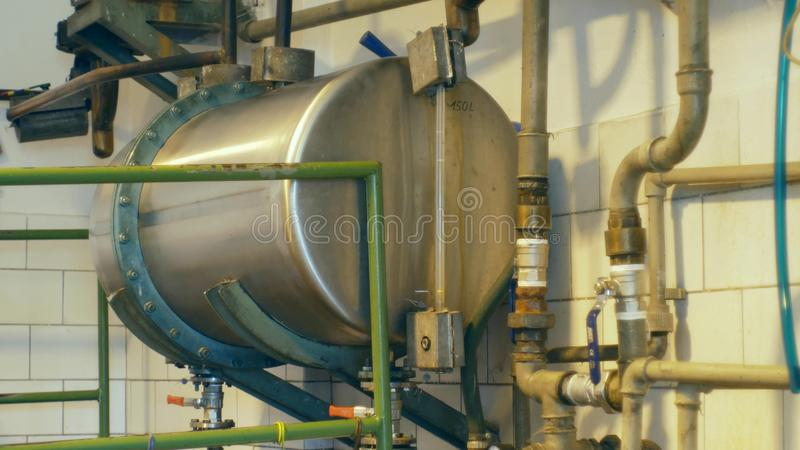 Growing distillery for the production of plum brandy by firing in a gas boiler, alembic pot still during process of. Distillation flow fresh plum brandy steel royalty free stock photos