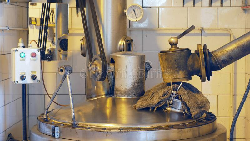 Growing distillery for the production of plum brandy by firing in a gas boiler, alembic pot still during process of. Distillation flow fresh plum brandy steel stock photos