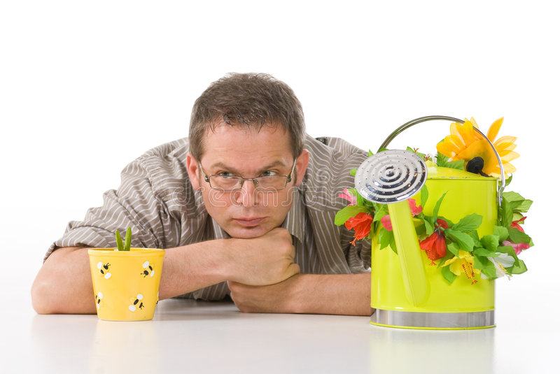 Growing Plants. A man with a watering can lying down, keenly waiting for his potted plant to grow royalty free stock photography