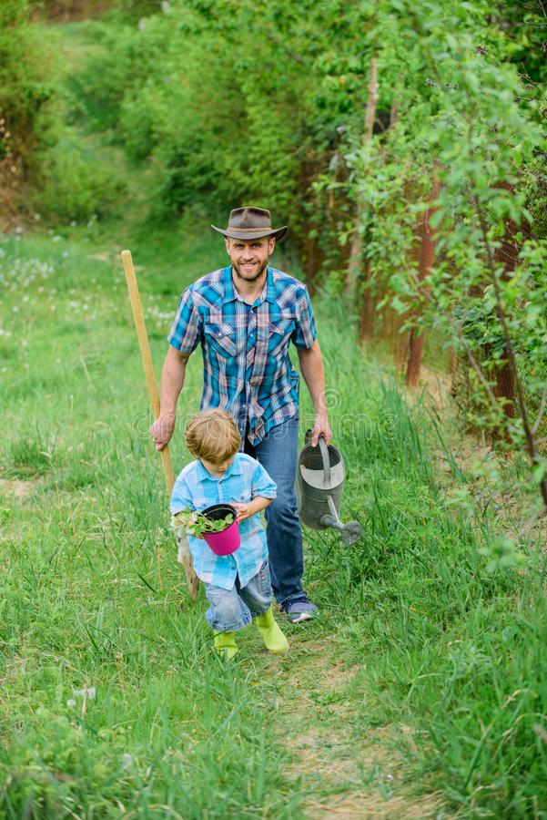 Growing plants. Boy and father in nature with watering can and shovel. Dad teaching son care plants. Arbor day. Planting. Trees. Tree planting tradition. Little royalty free stock photo