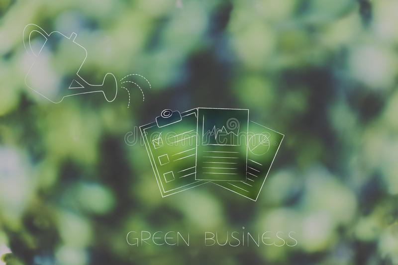 Watering can and business documents going green, ecology concept royalty free stock photo