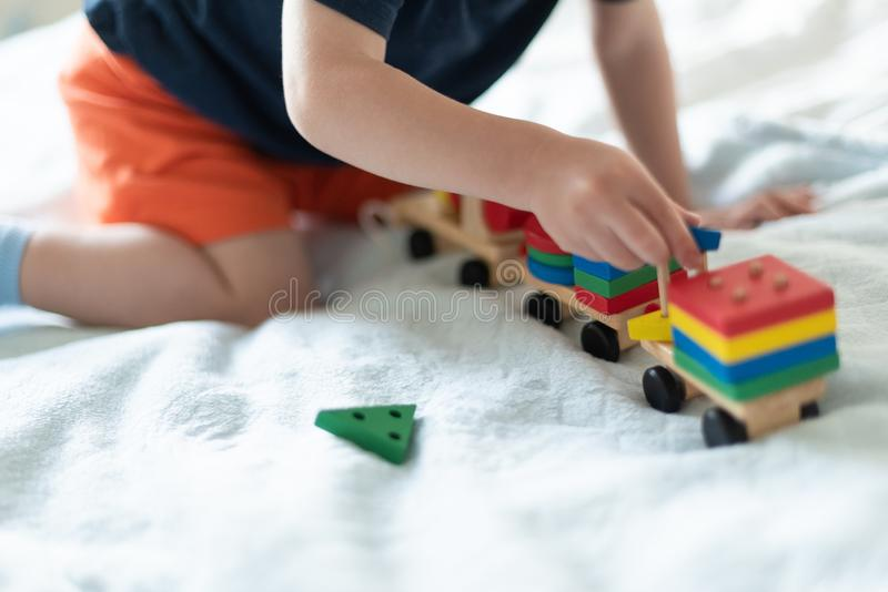 Growing up and kids leisure concept. A child playing with a colored wooden train. Kid builds constructor. Without face royalty free stock photo