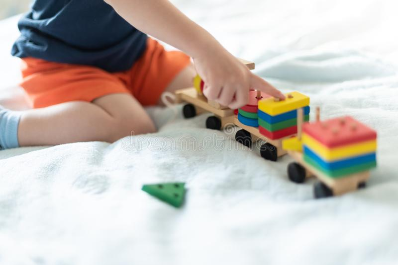 Growing up and kids leisure concept. A child playing with a colored wooden train. Kid builds constructor. Without face. Selective royalty free stock photo