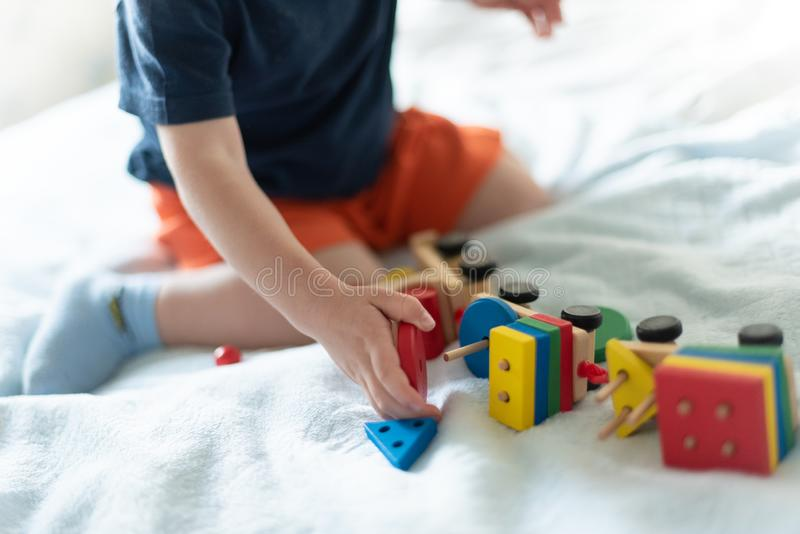 Growing up and kids leisure concept. A child playing with a colored wooden train. Kid builds constructor. Without face stock photos