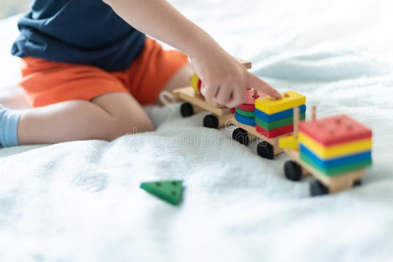 Growing up and kids leisure concept. A child playing with a colored wooden train. Kid builds constructor royalty free stock photos