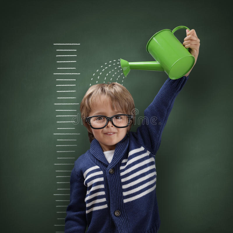 Growing up. Young boy trying to make himself taller with watering can measuring his growth in height against a blackboard scale royalty free stock photos