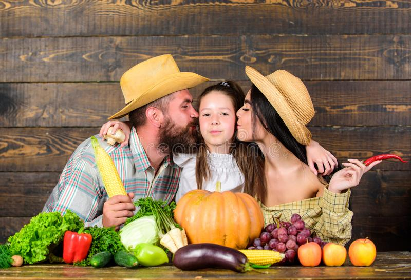 Grown with love. Family farmers with harvest wooden background. Family rustic style farmers at market with vegetables. Fruits and greenery. Parents and daughter stock photo