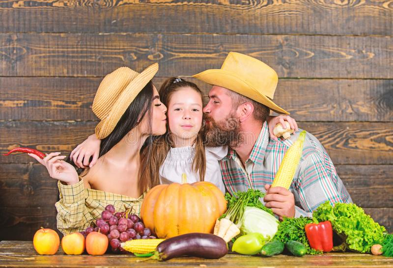 Grown with love. Family farmers with harvest wooden background. Family rustic style farmers at market with vegetables. Fruits and greenery. Parents and daughter stock image