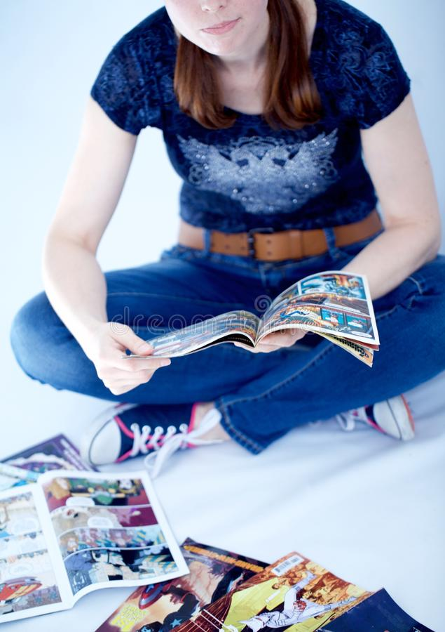 Adult woman reading comics books. A grown up woman reads some comic book sitting down stock image