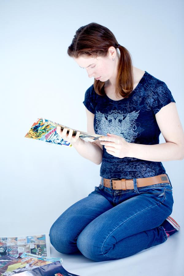 Adult woman reading comics books. A grown up woman reads some comic books sitting on the floor royalty free stock photo