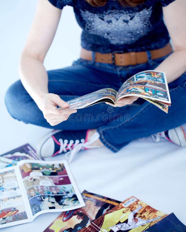 Adult woman reading comics books. A grown up woman wearing jeans and teeshirt reads some comic book sitting down royalty free stock photos