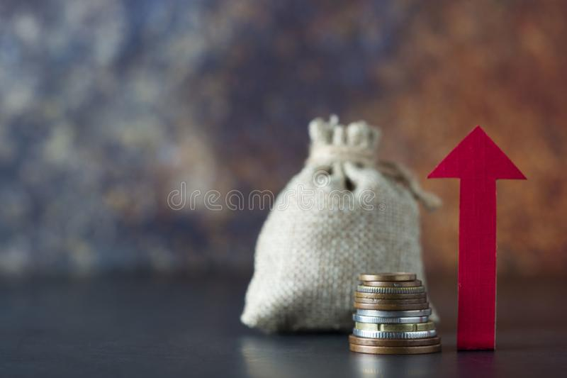 Growth, boost or increase your income with directional arrow, money and a bag over dark background. Financial concept. Copy space. Growth, boost or increase your royalty free stock photos
