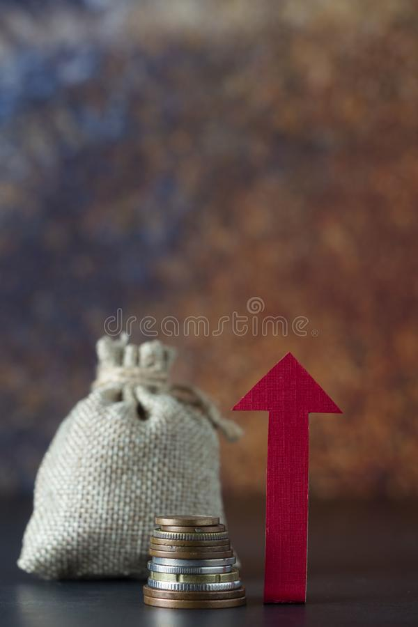 Growth, boost or increase your income with directional arrow, money and a bag over dark background. Financial concept. Copy space. Growth, boost or increase your royalty free stock photography